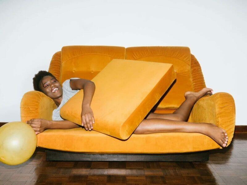 woman lying on orange sofa