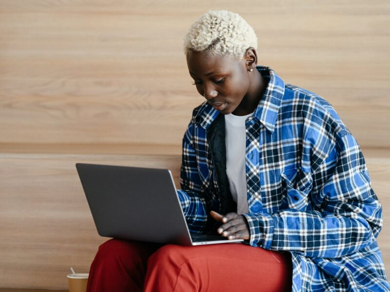young black woman with stylish haircut working with laptop